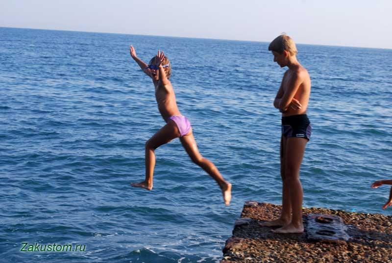Дети любят прыгать в море с пирсов