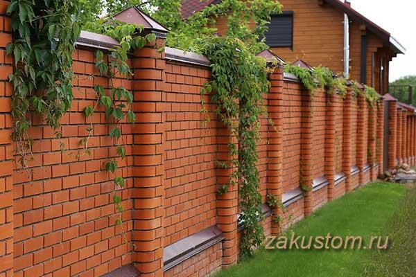 Высокий сплошной забор из кирпича у загородного дома